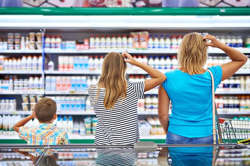 Famile steht vor dem Kühlregal im Supermarkt