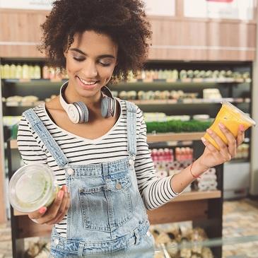junge Frau kauft Bio Lebensmittel ein
